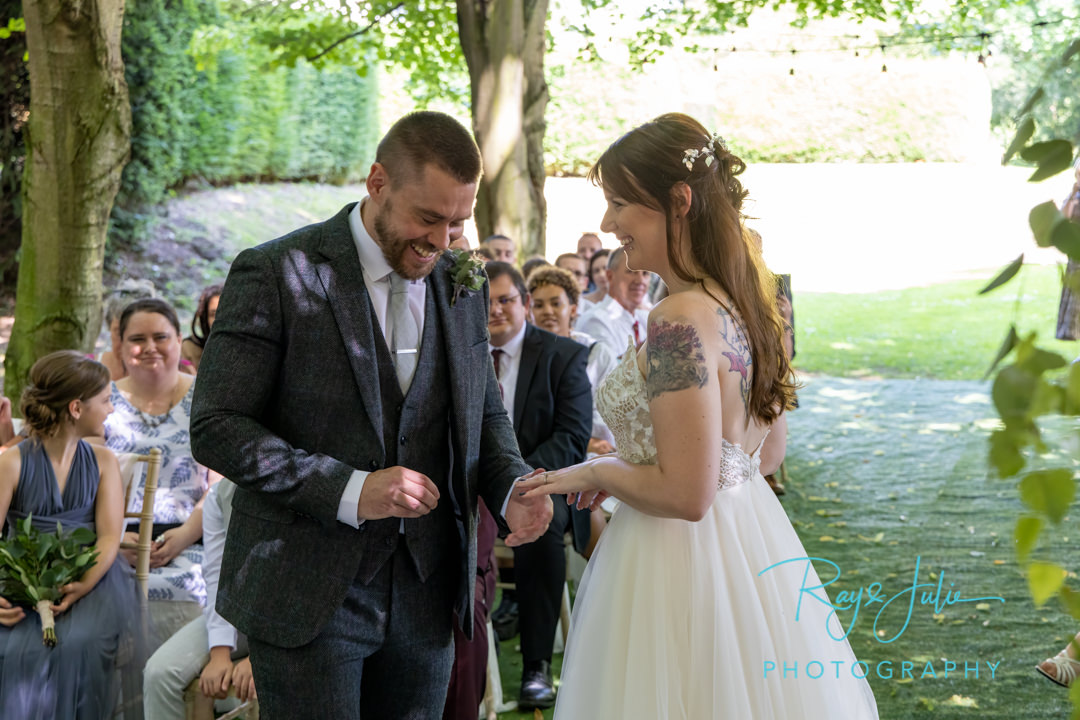 The ring exchange, bride and groom smiling