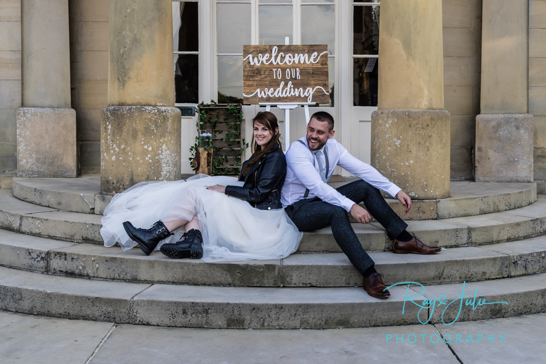 Welcome to our wedding. Bride and Groom sat on steps outside wedding venue. Bride with boot and leather jacket over her wedding dress