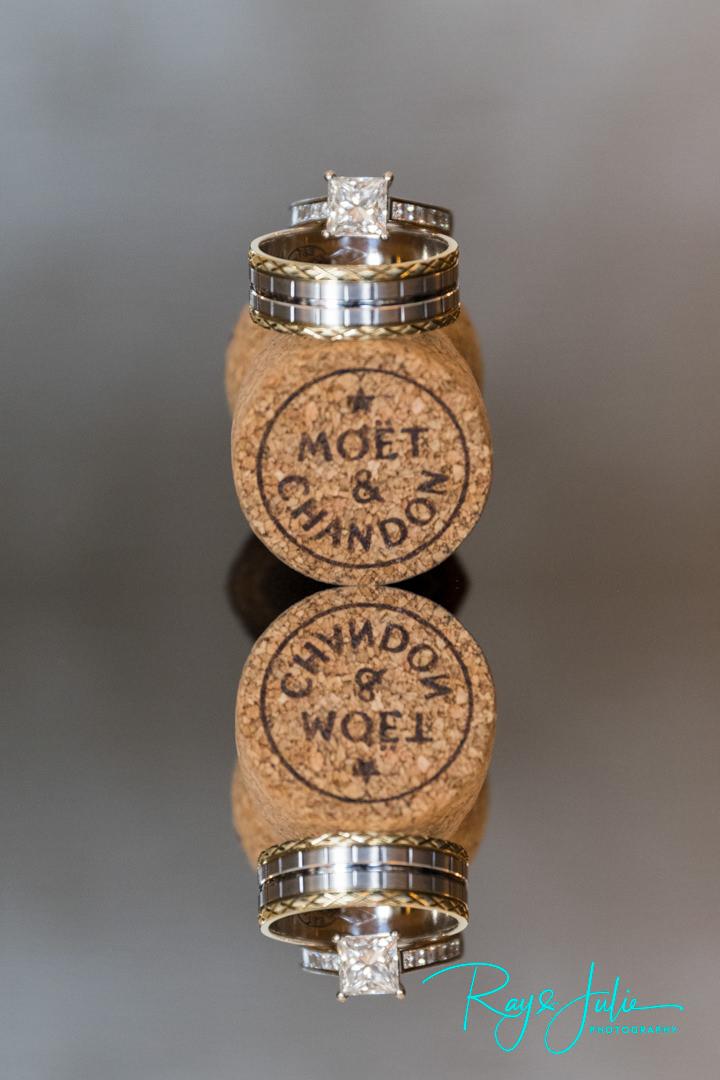 Stunning beautiful wedding rings reflection, balanced on Moet a cork