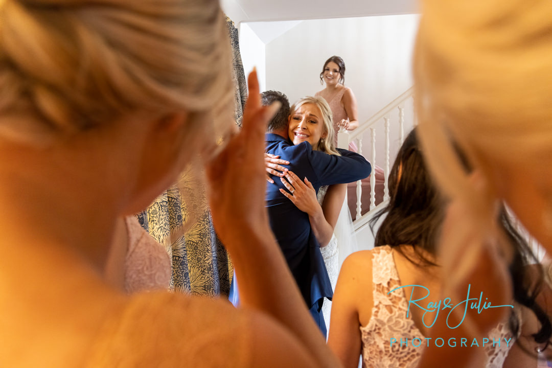 Emotional bride and dad first look hug in front of bridal party