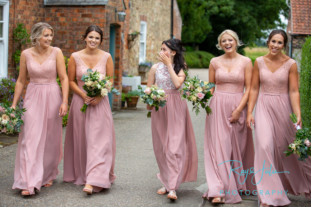 Bridesmaids laughing and smiling whilst walking