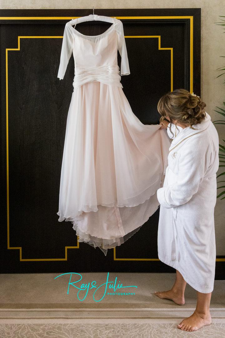 Bride looking at her Anita Masssarella Haute Couture pure silk chiffon wedding dress