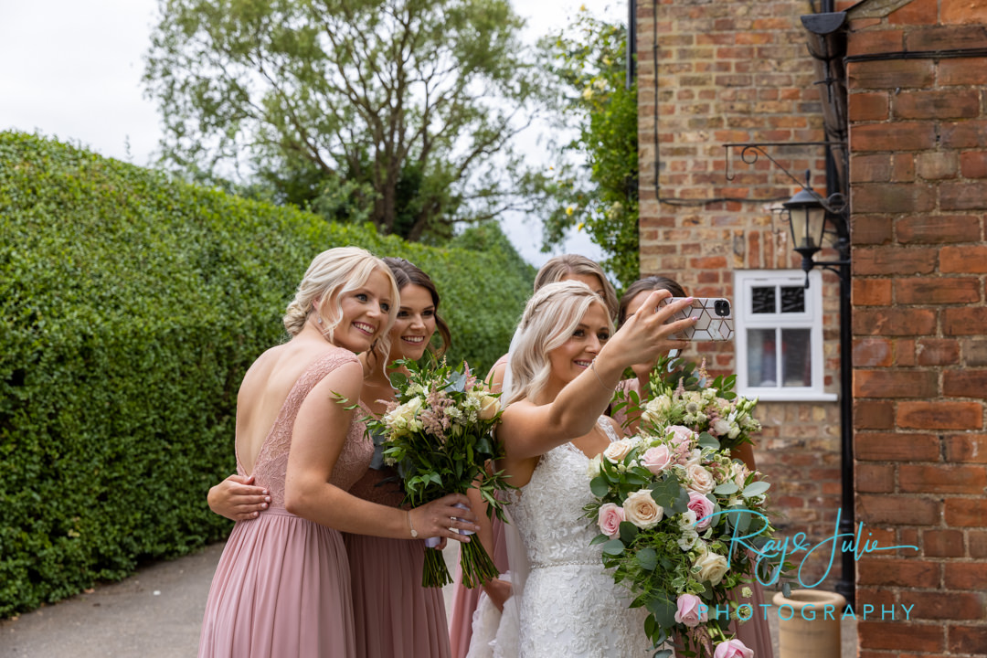 Bride and bridesmaids selfie time before wedding ceremony.