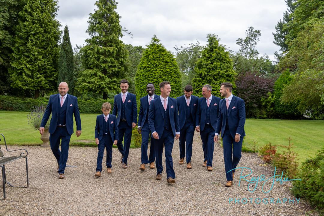 Groom and groomsmen walking having a laugh