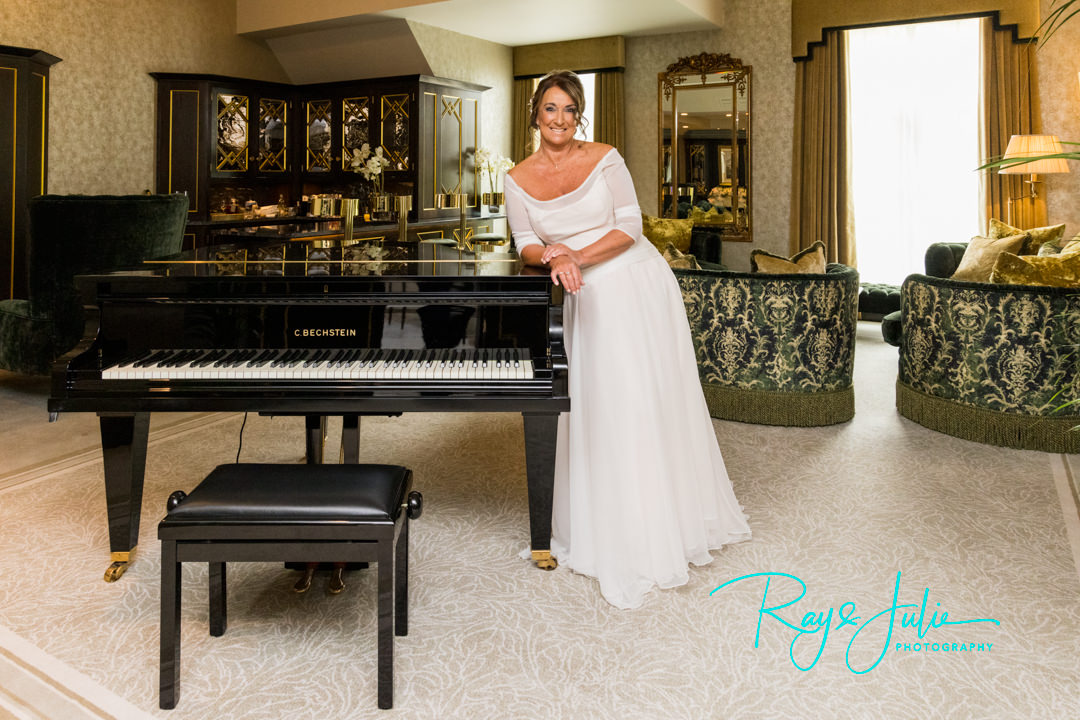 Bride smiling after bridal prep stood next to a piano in her pure silk chiffon wedding dress by Anita Massarella Design Couture. At Grantley Hall in the Presidential Suit