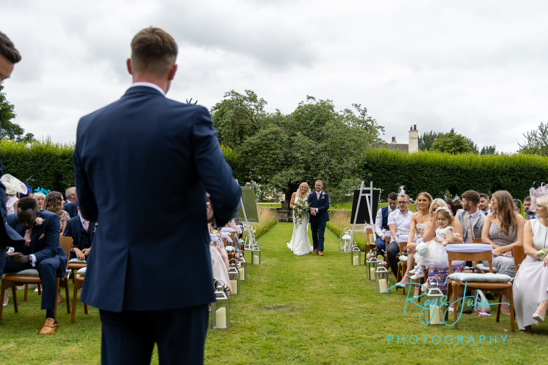Bride and dad walking to onlooking groom, at their outdoor wedding ceremony at Tickton Grange