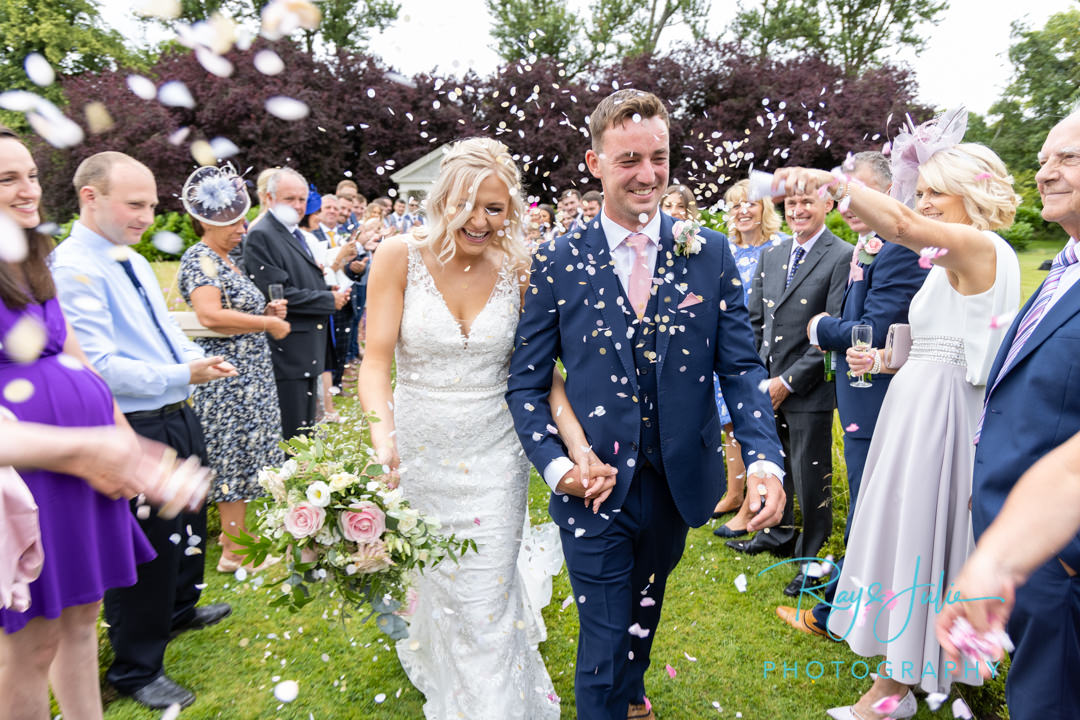 Confetti wedding photograph with bride, groom and guests. Yorkshire wedding venue.