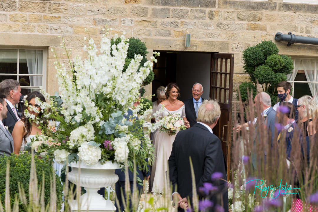 Bride and Father making their entrance to the outdoor wedding ceremony at Grantley Hall