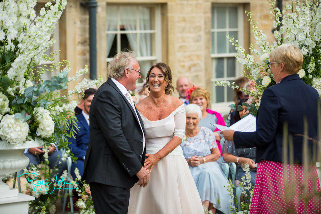 Bride and Groom laughing together during the wedding ceremony at Grantley Hall