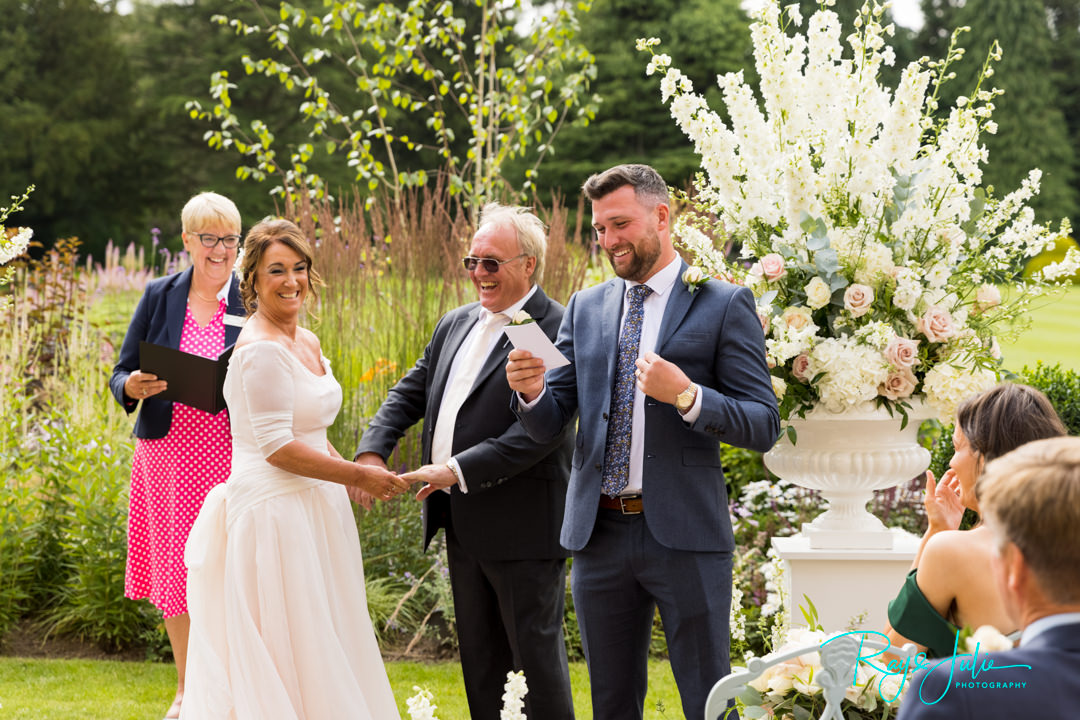 Bride and Groom smiling during a reading during there wedding ceremony at Grantley Hall