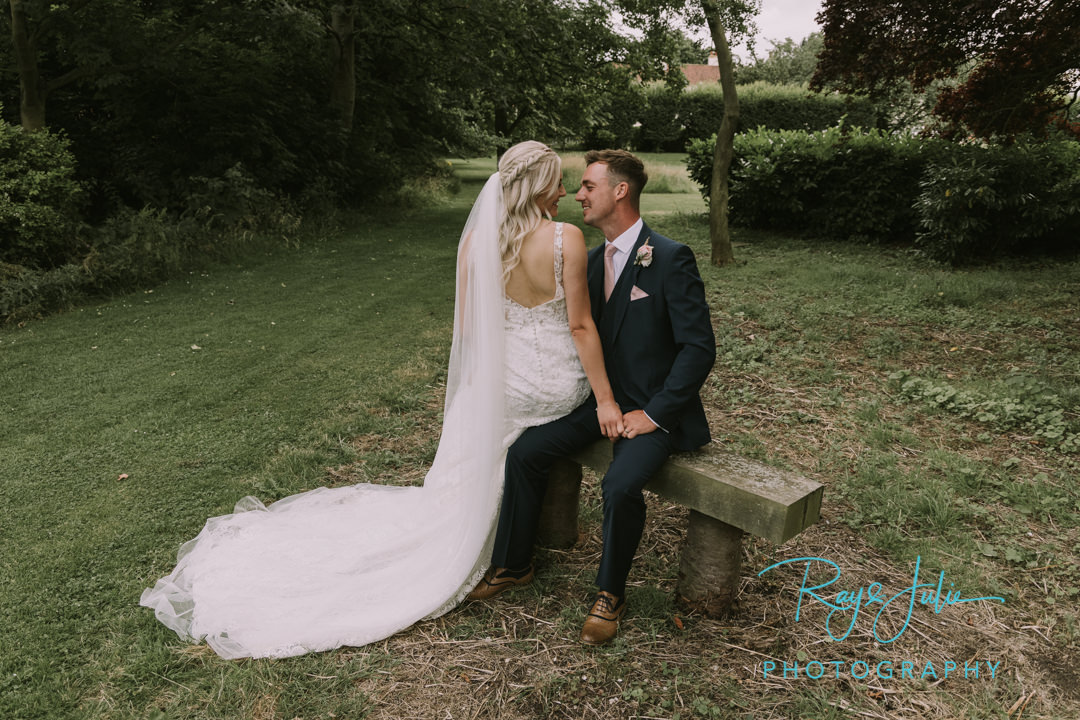Bride and Groom sat on a bench looking at each other. Outdoor summer wedding photograph captured at Tickton Grange East Riding of Yorkshire.