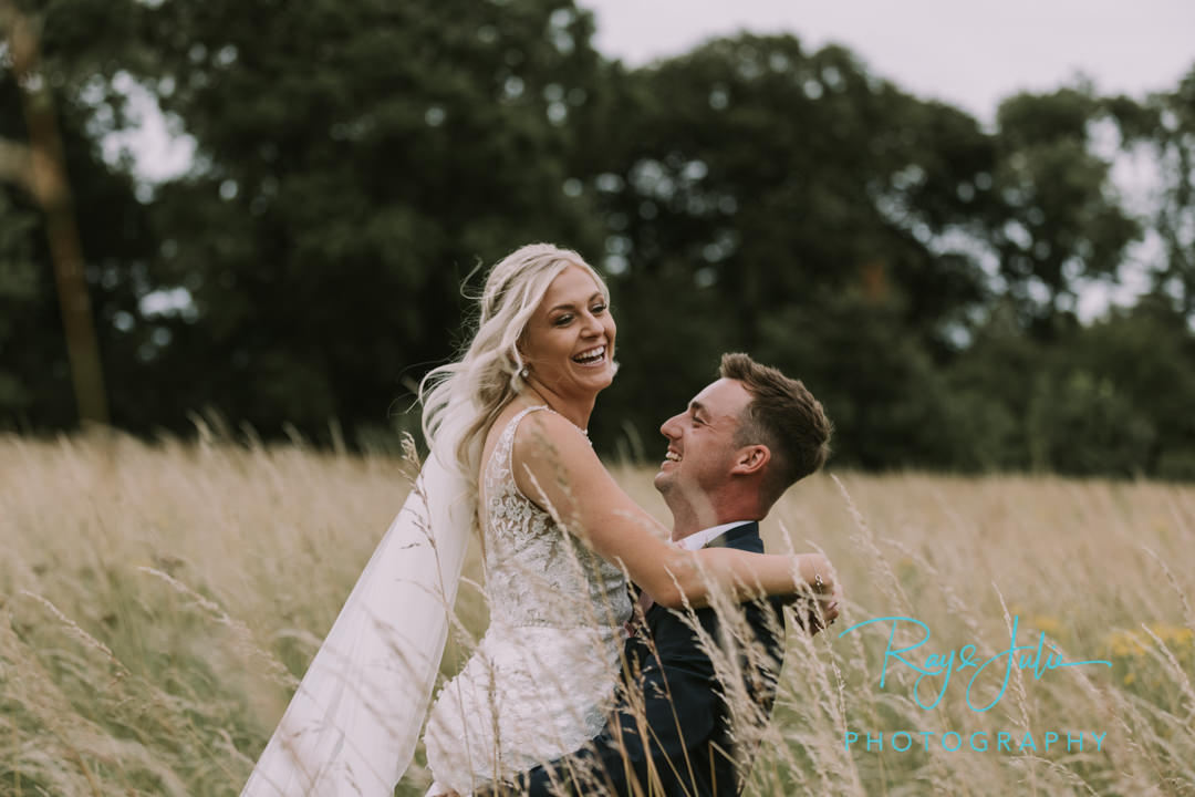 Groom picking up his happy bride in long grass