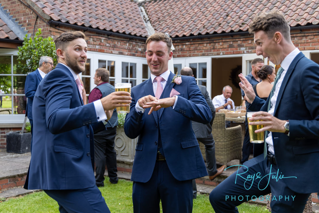 Groom showing off his wedding ring to wedding guests