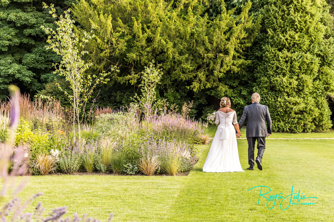 Bride and Groom walking hand in hand in the gardens at Grantley Hall