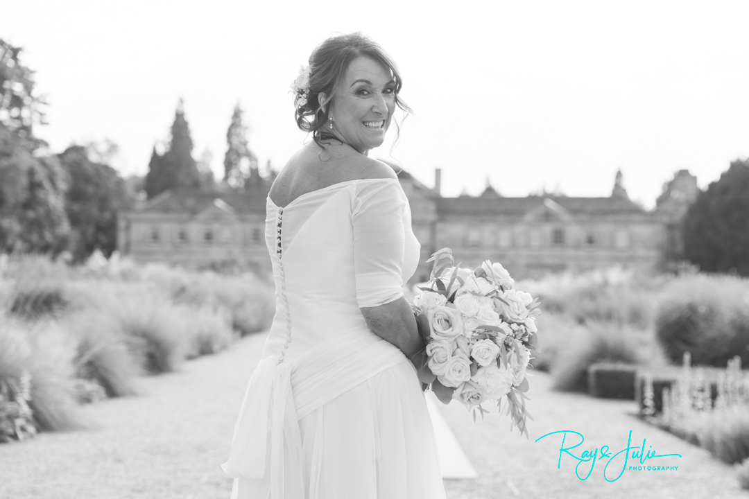 Beautiful bride in black and white holding a bouquet with Grantley Hall in the background