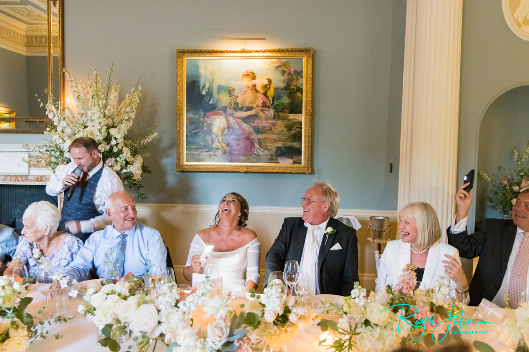 Bride laughing at The Best Singing Waiters whilst performing at their wedding reception at Grantley Hall