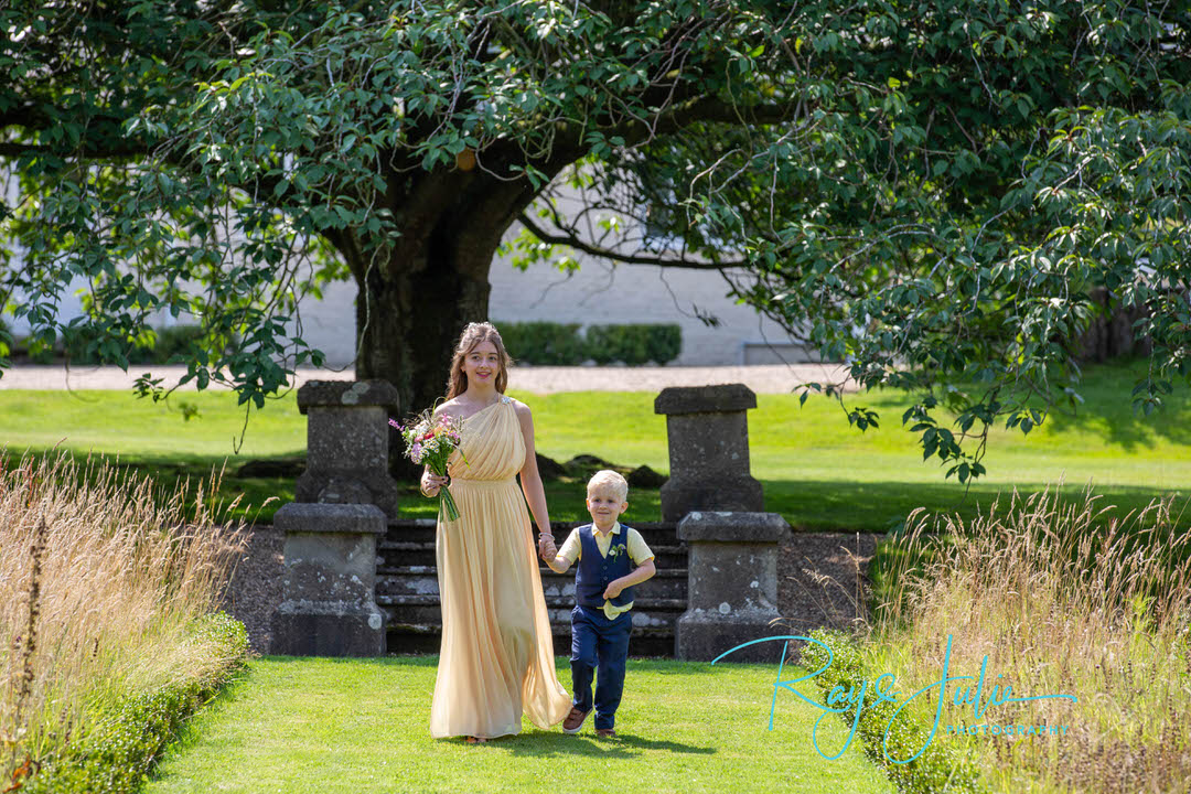 Bridesmaid and pageboy walking towards wedding ceremony outdoor wedding at Tickton Grange