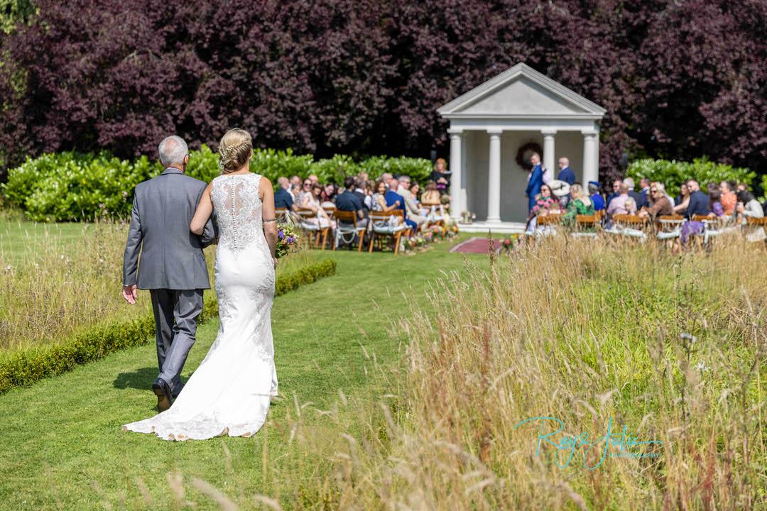 Bride and dad walking to groom - outdoor wedding at Tickton Grange