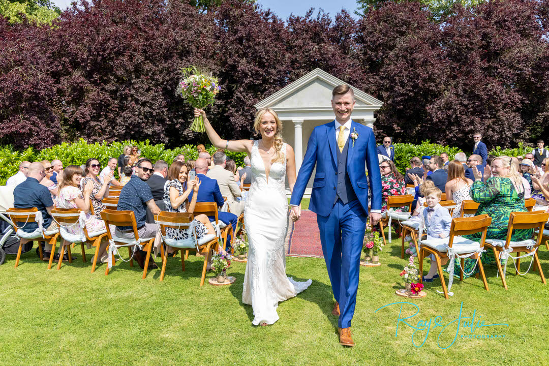 Bride and groom smiling after just getting married at Tickton Grange. Bride holding flowers in the air.