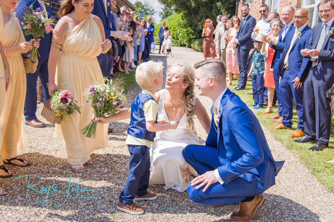 Bride and groom smiling at their son