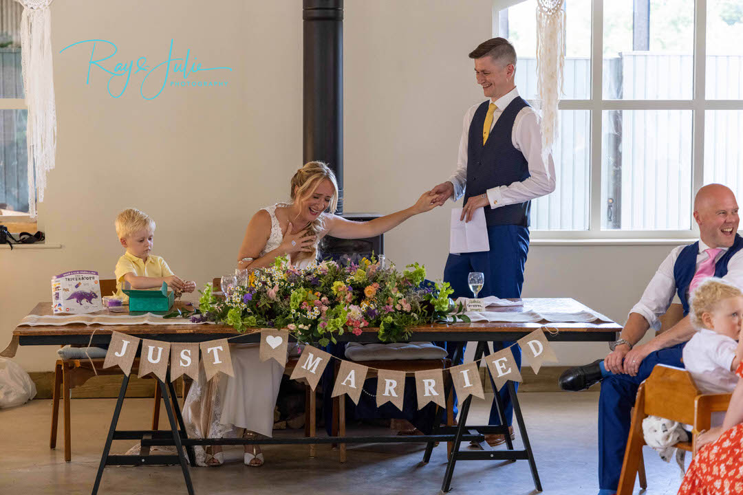 Bride laughing at grooms speech whilst holding hands