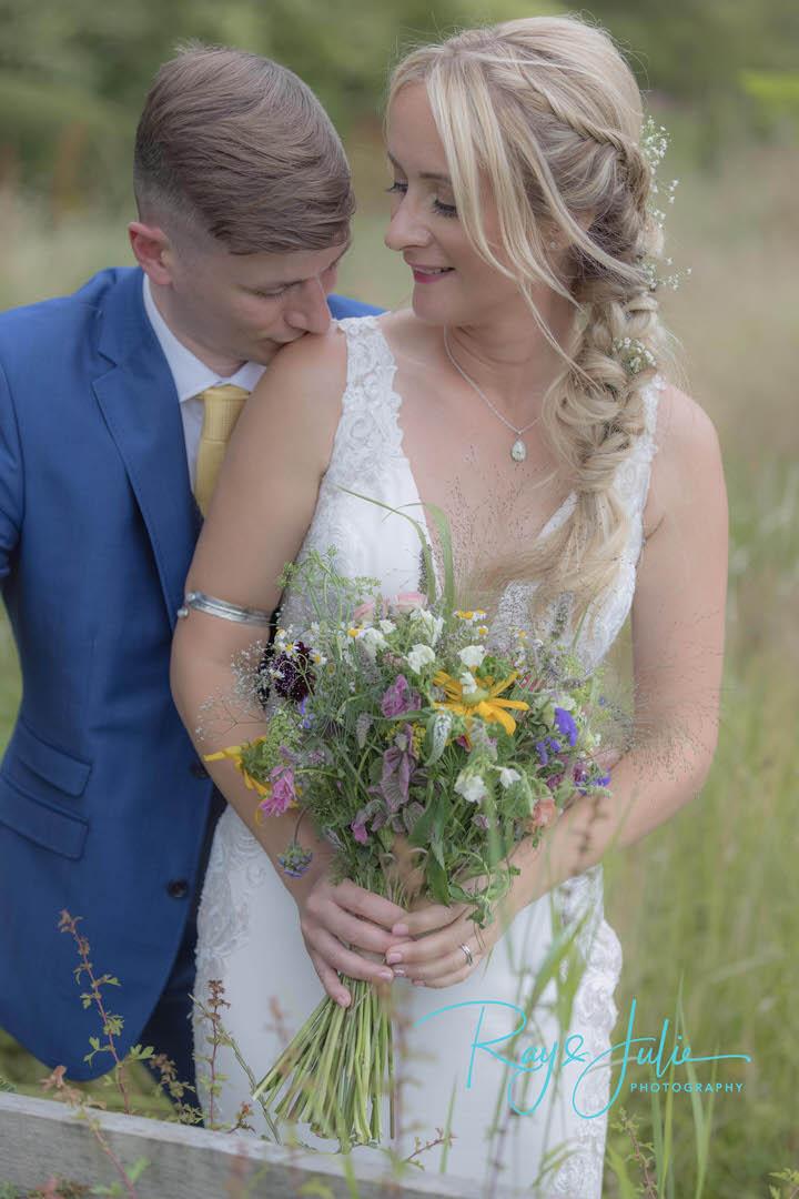 Beautiful bridal couple portrait. Bride holding wedding bouquet