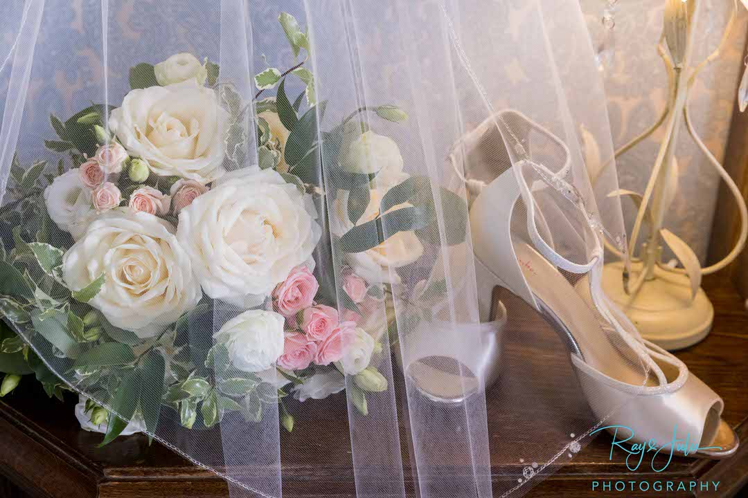 Brides wedding shoes veil and flowers