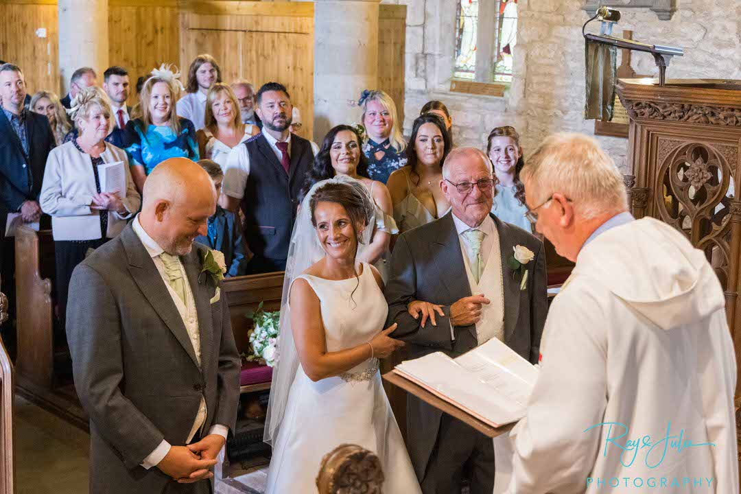 Bride smiling at groom at front of church at St Peters Church East Yorkshire