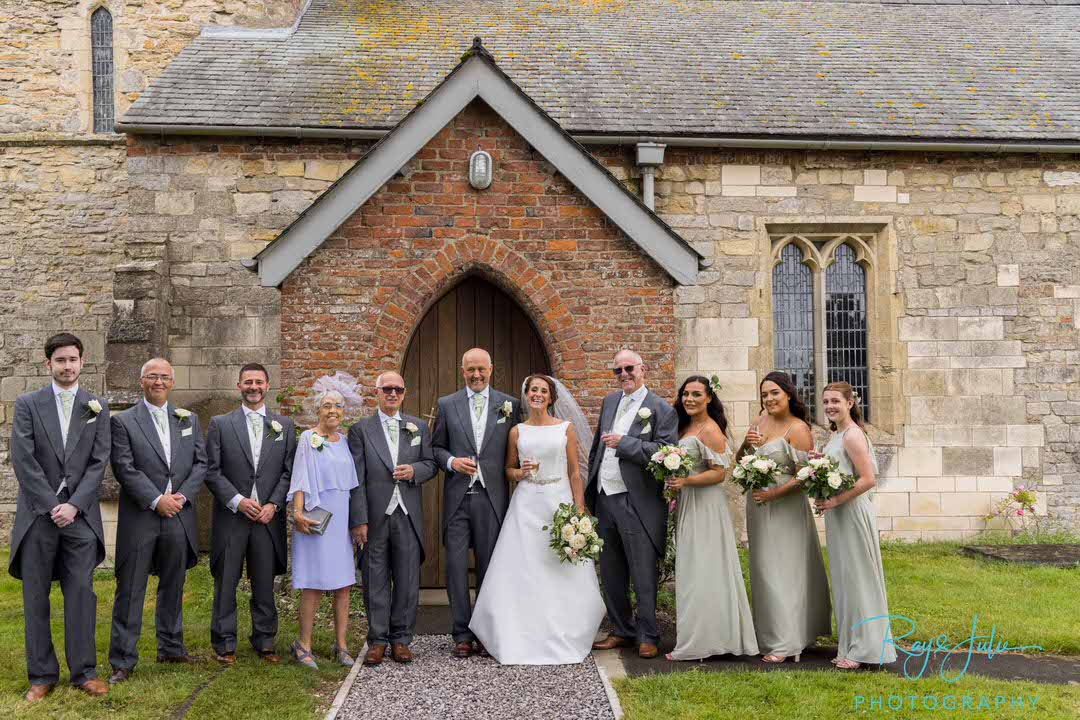 Wedding party group photo outside front of the church