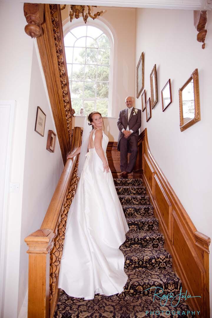 Wedding couple on the stairs at Rowley Manor Bride in a Deborah Moore wedding dress